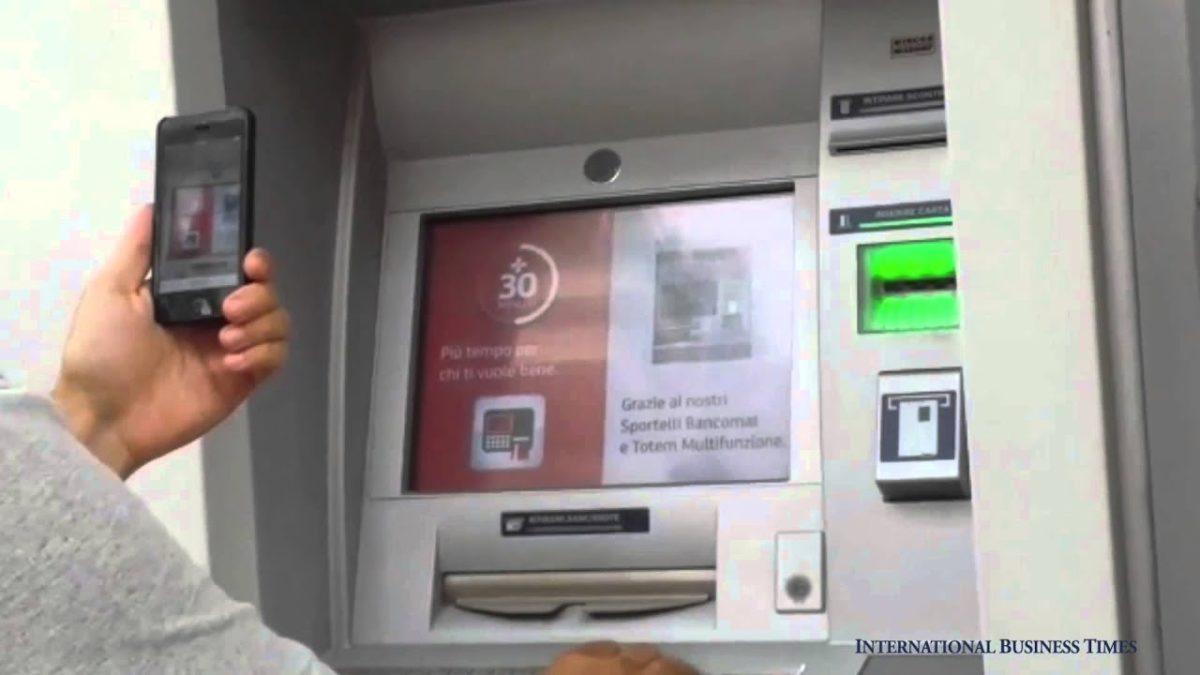 Persona con telefono effettua operazioni di prelievo davanti a sportello bancomat