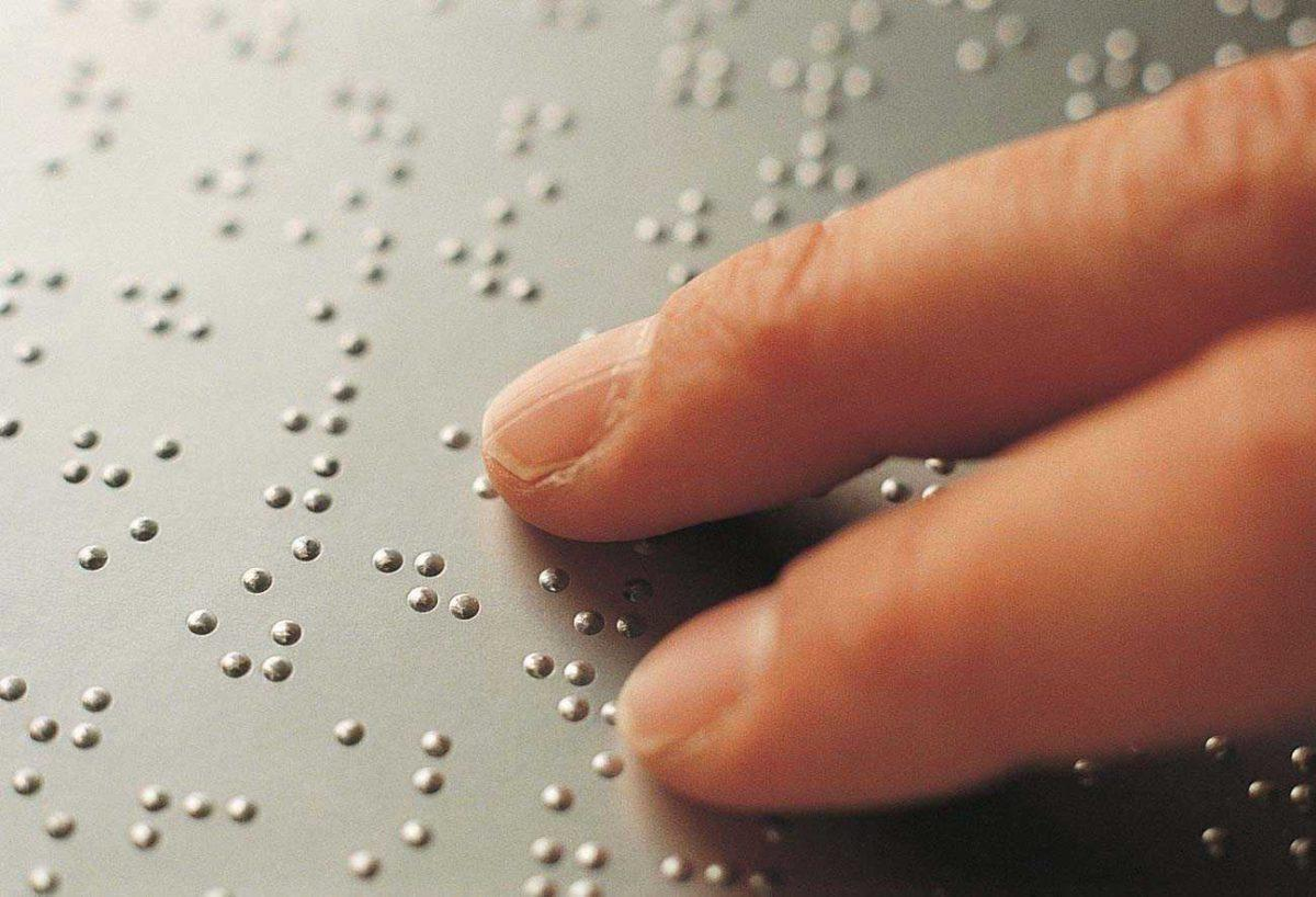 dita leggono testo in braille