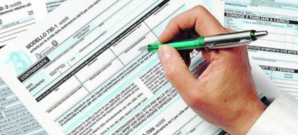 Una persona compila a mano la dichiarazione dei redditi