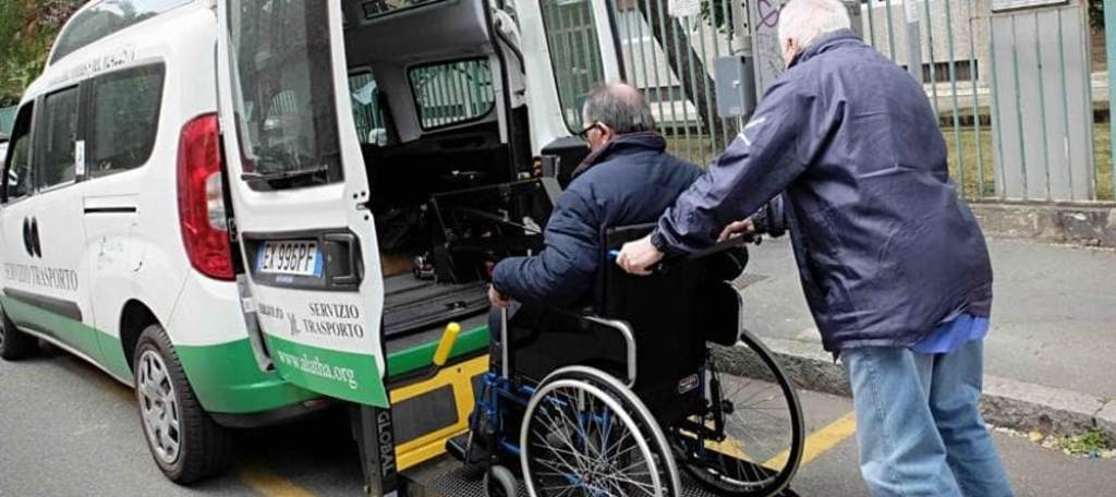 Un operatore aiuta una persona in carrozzina a salire su un mezzo attrezzato