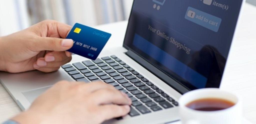 Una persona con carta di credito davanti a pc portatile