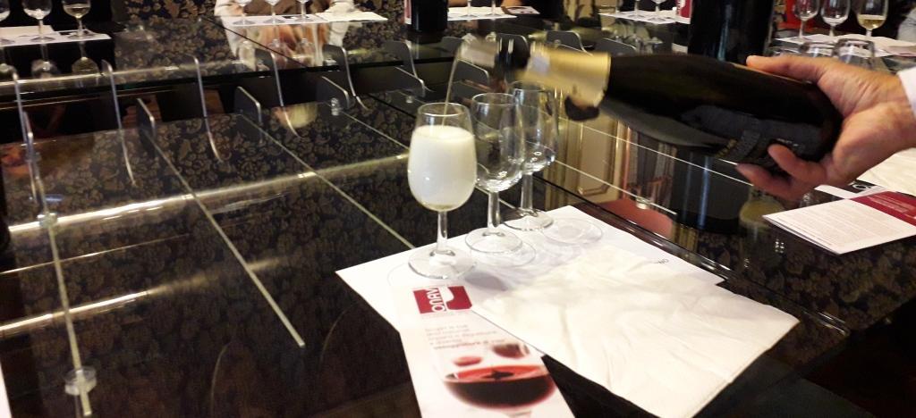 Un mescitore versa vino bianco in un calice da degustazione