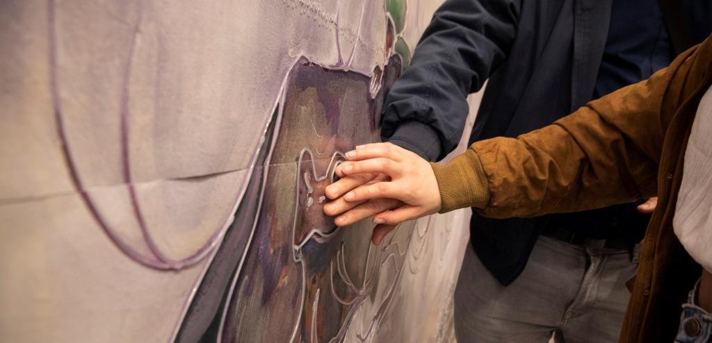 Mani toccano parete con opera d'arte - Fondazione Sandretto