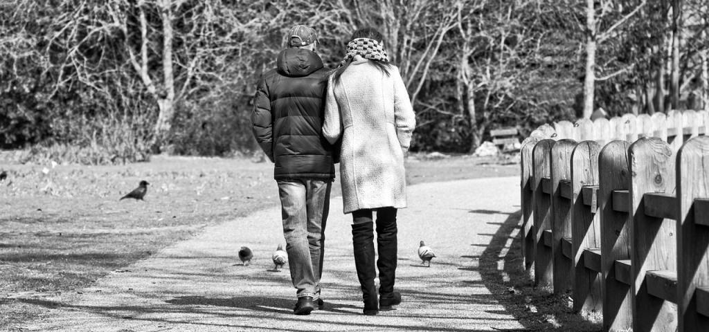 Due persone, uomo e donna, camminano sotto braccio lungo un viale