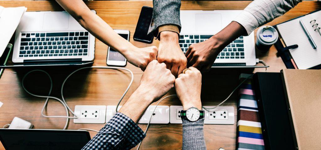 Tavolo con strumenti di pc, smartphone e mani che si incontrano