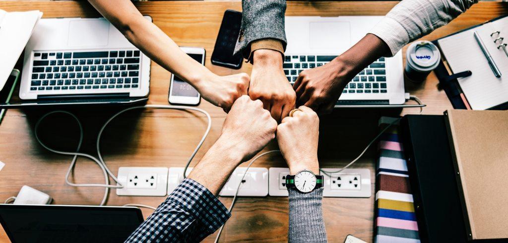 persone avvicinano le mani su scrivania con computer e telefoni