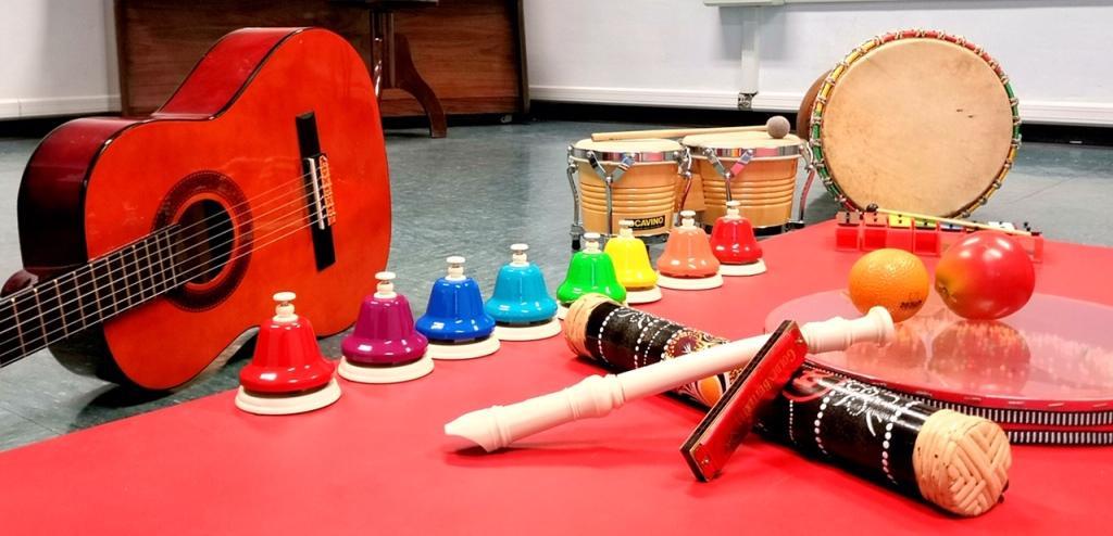 in primo piano chitarra, campanelle percussioni e altri strumenti musicali