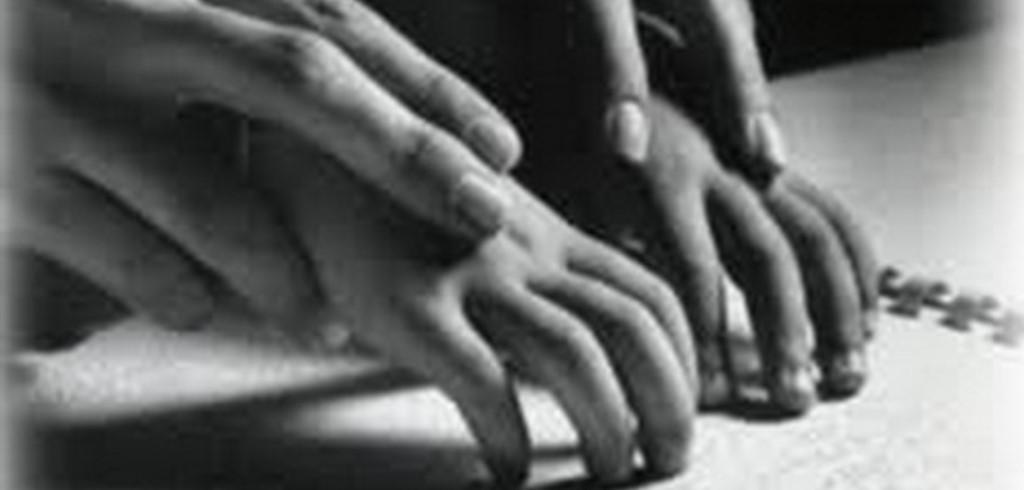 Mani insegnante guidano mani bambino su foglio braille