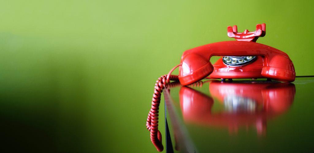 Telefono con cornetta appoggiato su un tavolo