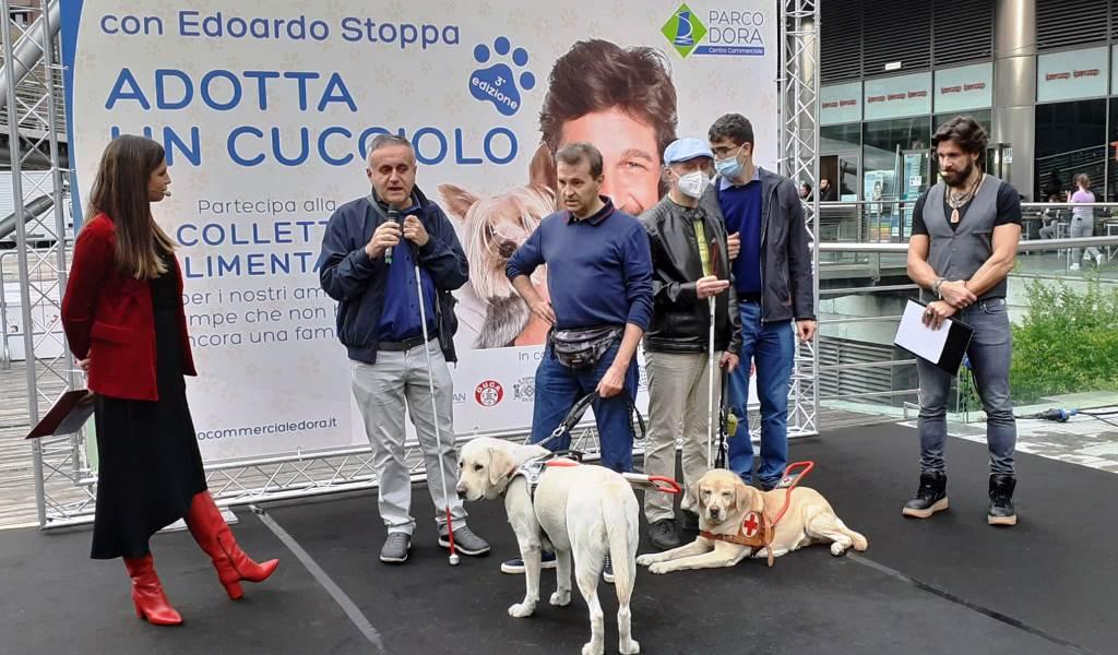 """Manifestazione """"Adotta un cucciolo"""". Sul palco, con Edoardo Stoppa, presidente UICI Torino, cani guida e conduttori"""
